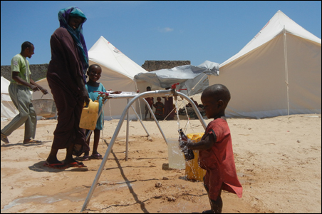 A child at Rajo Camp collects water provided by donors in Minnesota