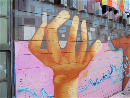 Mural depicts hands emerging from the Mississippi River.