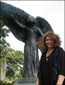 "Julie Kramer next to Mario Korbel's ""Black Angel"" statue in Oakland Cemetery, Iowa City"
