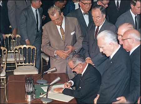 Sens. Everett Dirksen and Hubert Humphrey and Speaker of the House John McCormack watch as President Lyndon Johnson signs the 1964 Civil Rights Act.