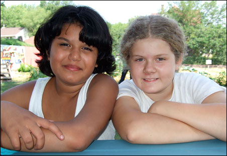 Kiara Martinez, 12, left, and Nora Murphy, 10, get time to to bond while keeping busy weeding, watering and harvesting at the urban garden.