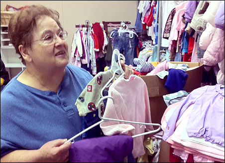Hanging up kids' clothes in preparation for the Oct. 8 grand opening is volunteer Eileen Gogolakis.