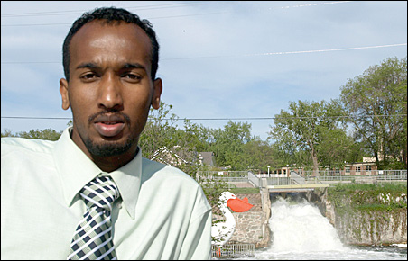 Abdirashid Nuur stands near the namesake statue and waterfalls in his new home.