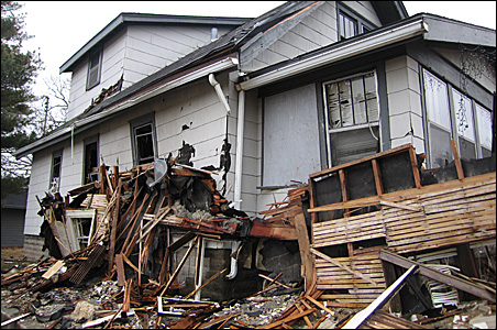 The wall from a house at 3206 Colfax Ave. N., which blew up March 26, smashed into the condemned building next door.