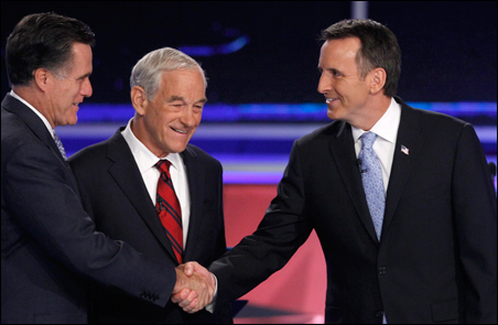 Former Govs. Mitt Romney and Tim Pawlenty shaking hands prior to the debate as Rep. Ron Paul looks on.