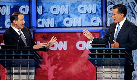 Former Arkansas Governor Mike Huckabee (L) and former Massachusetts Governor Mitt Romney