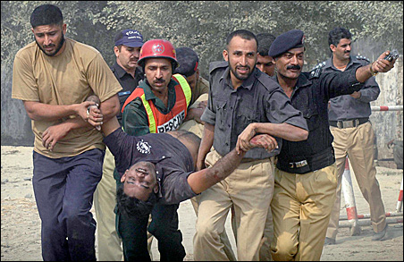 Police and rescue workers carry the body of a dead policeman from the Manawa police training centre after it was attacked by gunmen in Lahore on Thursday, Oct. 15, 2009.