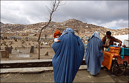 An Afghan woman clad in burqa holds her child as another woman buys coconut at a cemetery in Kabul