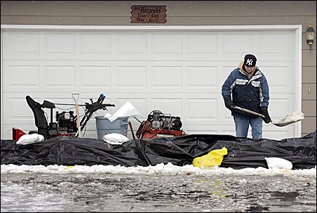 Travis Hersrud shovels slush from behind the sandbag dike