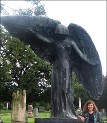 "Julie Kramer next to Mario Korbel's ""Black Angel"" statue in Oakland Cemetery, Iowa City."