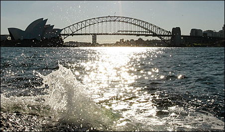 Waves crash over rocks in Sydney Harbour near the city's famous bridge and opera house.