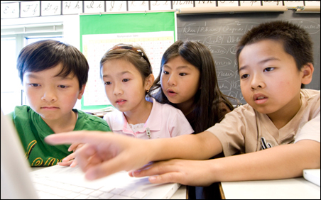 Left to right, Phan, Nhu, Chyna and Isaac track the growth of monarch butterflies using a spreadsheet in Carol Fischer's fourth-grade class at Osseo's Weaver Lake elementary school.