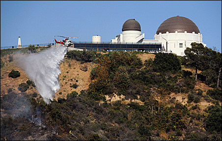 A helicopter makes a water drop as firefighters try to contain a brushfire near the Griffith Observatory in Los Angeles earlier this month.