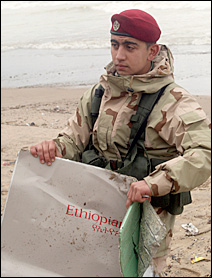A Lebanese soldier carries a piece of wreckage at Khaldeh beach, south of Beirut.