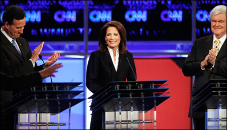 Former Sen. Rick Santorum, left, and former House Speaker Newt Gingrich, right, applaud Rep. Michelle Bachmann as she is introduced at the New Hampshire debate.