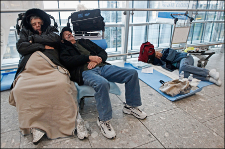 Airline passengers sleep in Terminal 5 at Heathrow Airport, in west London.