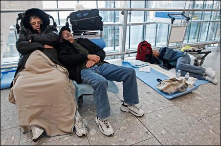 Airline passengers sleep in Terminal 5 at Heathrow Airport, in west London.