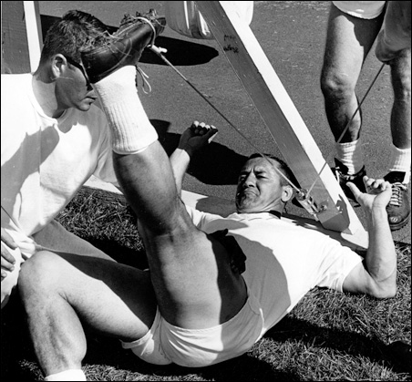 Packers fullback Jim Taylor works out, his raised leg partially obscuring Harrington.