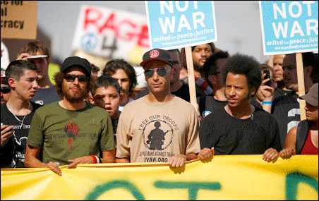 Members of the band Rage Against the Machine lead a march through Denver on Wednesday. The band plays Sept. 3 at Target Center.