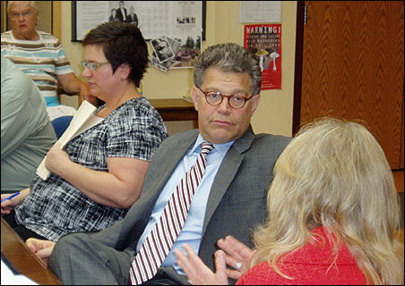Sen. Al Franken listens as Gayle Kvenvold explains the economic benefits of keeping seniors in their homes.