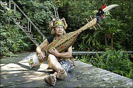 """An Orang Ulu or """"upriver people"""" from Sarawak's indigenous tribe plays a musical instrument called """"sape"""" at Sarawak Cultural Village in Malaysia's Borneo state of Sarawak."""