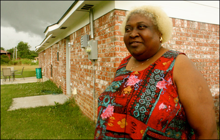 Debra Richardson stands next to her house in the Mississippi Delta where she struggles with diabetes and other chronic illnesses.