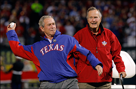 Former President George H.W. Bush, right, watches as his son, former President George W. Bush, throws a ceremonial first pitch prior to the start of Game 4 of the World Series.