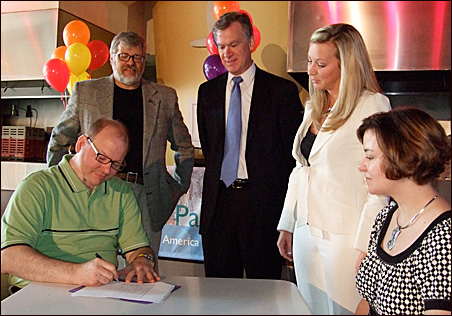 Pop! co-owners Clark and Leslie Knutson (seated) make things official Thursday. On hand for the ceremony were, from left, St. Paul City Council Member Dave Thune, Mayor Chris Coleman and Sarah Martin, a broker for Welsh Cos.