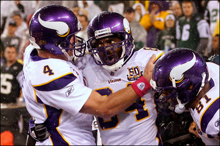 Brett Favre, left, celebrates with receiver Randy Moss after Moss caught Favre's 500th touchdown pass during the second half of Monday night's game versus the New York Jets.