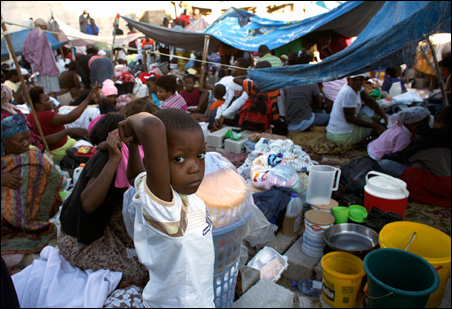 A boy stands at an open area camp in Port-au-Prince where people are staying following Tuesday's major earthquake.