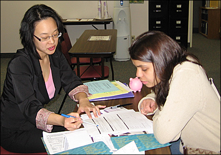 Eva Song Margolis of AccountAbility Minnesota helps with an Express Refund Loan application.