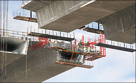 Workers prepare to install the last segment of the bridge.