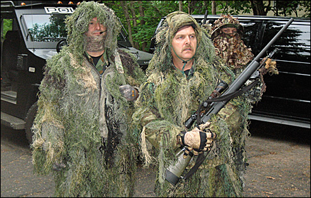 Police snipers dressed in lightweight ghillie camouflage suits wait for the next training session to begin.