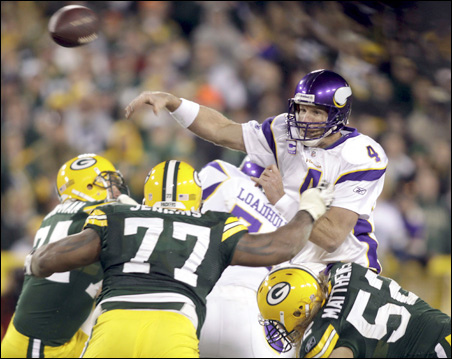 Under pressure from defensive end Cullen Jenkins, center, and linebacker Clay Matthews, right, Vikings quarterback Brett Favre throws an incomplete pass during the fourth quarter of Sunday's game.
