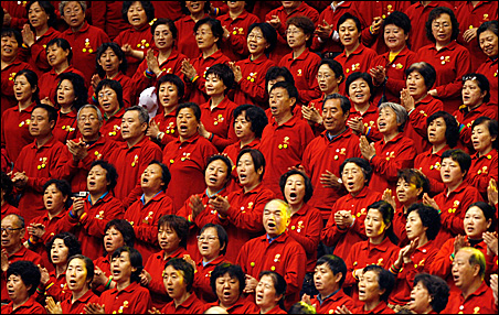 Enthusiastic volunteers for the Beijing Olympics cheer during a May rally as Chinese officials prepare to showcase their country next month. The Games will use 100,000 volunteers, with another 400,000 citizens providing services through the city.