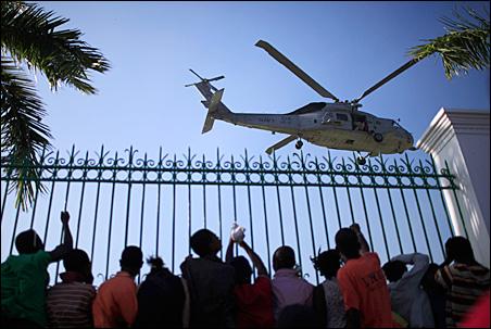 Crowds watch as a Sea Hawk helicopter with soldiers from the 82nd Airborne lands near the damaged Presidential Palace in Port-au-Prince on Tuesday.