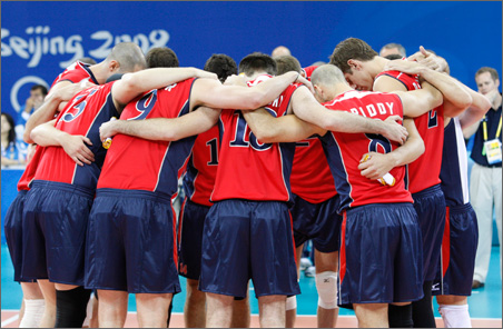 With their coach tending to family matters, members of the U.S. men's volleyball team observe a moment of silence before their first match.