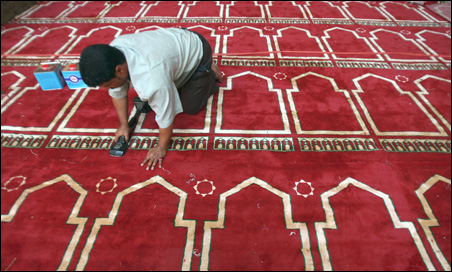 A worker puts down new carpet at the Sultan Hassan Mosque, in the old Islamic area of Cairo, in preparation for President Obama's visit to the Egyptian capital.