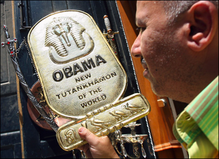 A souvenir shop's owner displays a recently made metal plaque honoring President Obama in Cairo Monday.