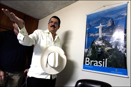 Honduras' ousted President Manuel Zelaya waves during a meeting with his representatives inside the Brazilian embassy in Tegucigalpa October 19, 2009.