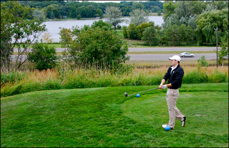 Justin Buoen watches his drive from the tee where tipsy pros used to hit balls into Keller Lake across the highway.