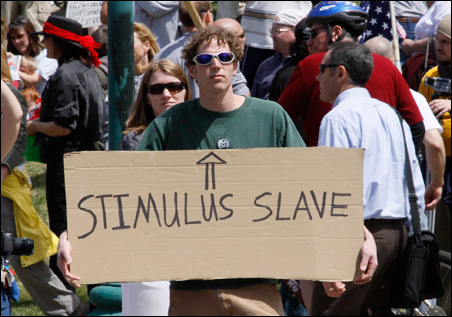 """Protesters wave signs raising the slavery issue at a """"tea party"""" protest on the grounds of the Colorado State Capitol in Denver, April 15, 2009."""