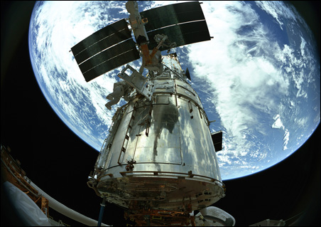 Astronauts at work on the Hubble Space Telescope.