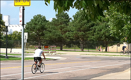 A cyclist on 11th Street South heads toward the area across West River Road where a memorial garden may be sited.