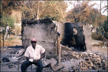 An Anuak man in Gambella following the massacre there on December 13, 2003. His house, behind him, was burned down by Ethiopian soldiers on that day.