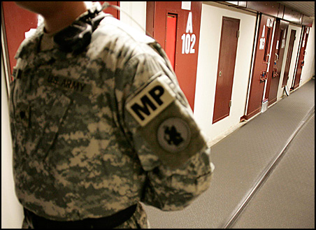 A U.S. Army guard stands in a corridor of cells in Camp Five