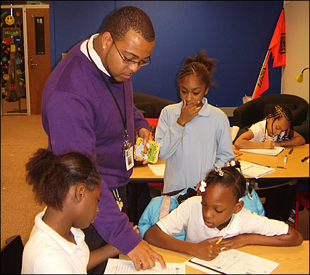 Project Spirit lead teacher William Hill helps students, from left, Keyira Miles, grade four, and Jonicia Henderson-Carr, grade five, while fifth-grader Talajah Davis looks on.