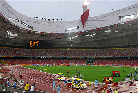 Volunteers prepare Thursday for the start of this weekend's Olympic track and field competition inside Beijing's National Stadium.