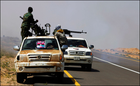 Rebel fighters flee on trucks under fire after they were ambushed by forces loyal to Muammar Gaddafi some 75 miles east of Sirte on Monday.