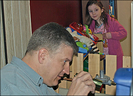 Jemma Streich, age 5, watches energy auditor Randy Hansen checking out the Streichs' furnace.